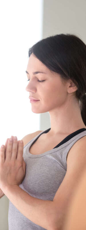 Young attractive woman practicing yoga with group of students, doing meditation exercise, relaxation pose with namaste, working out wearing sportswear, indoor close up, yoga club. Well-being concept