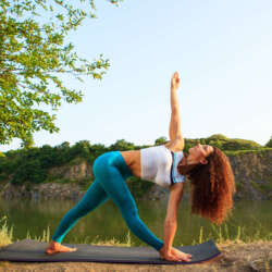 Young woman is practicing yoga at river